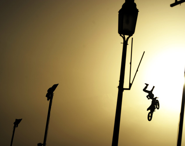 An extreme motorcycle professional flies through the air during a motorcycle street show near India Gate in New Delhi.