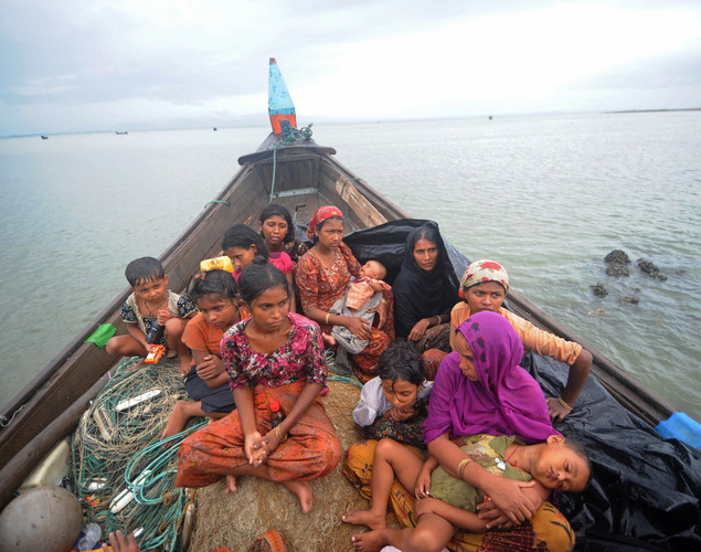 Rohingya Muslims, trying to cross the Naf river into Bangladesh to escape sectarian violence in Myanmar, look on from an intercepted boat in Teknaf.