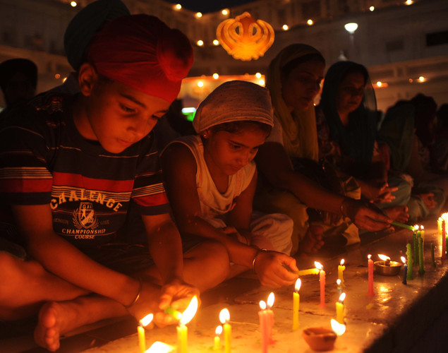 Indian Sikh devotees light candles at the illuminated Golden Temple in Amritsar.
