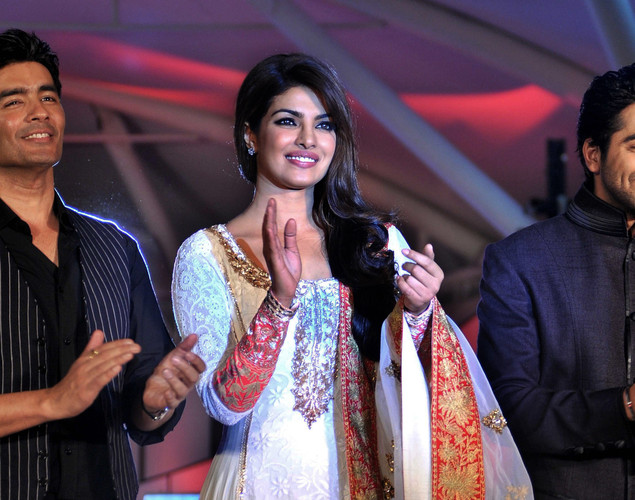 Bollywood film actress Priyanka Chopra walks the ramp with actor Ayushmann Khurrana (R) during the seventh annual Pidilite-CPAA Charity Fashion Show showcasing designers Manish Malhotra (L) and Shaina NC in support of the Cancer Patients Aid Association.