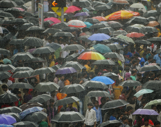 Huge crowds cover themselves with umbrellas in heavy rain during a funeral procession of Bollywood superstar Rajesh Khanna in Mumbai.