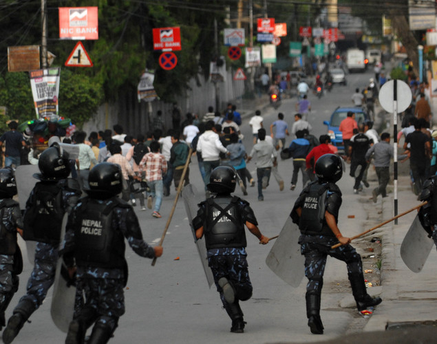 Nepalese riot police chase Youth Force Wing activists of the Communist Party of Nepal (UML) during a protest demanding the resignation of Prime Minister Baburam Bhattarai in Kathmandu.