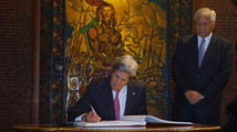 U.S. Secretary of State John Kerry signs a guest book as Philippines' Foreign Secretary Albert del Rosario looks on in Manila