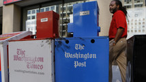 Washington Post and Washington Times newspaper boxes are pictured outside the entrance to the Washington Post headquarters in Washington