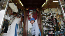 A man stands in front of a store window with a mannequin and other items in the streets of downtown Guatemala City