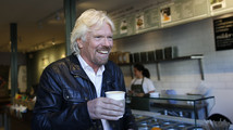 Sir Richard Branson, Founder of Virgin Group, buys coffee before a seminar about the Virgin StartUp scheme for young entrepreneurs at Box Park in east London