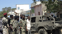 Somali policemen stand next to a damaged car at the scene of an explosion in Baladweyne in central Somalia