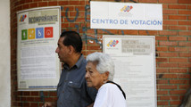 An elderly woman is helped by a man as she arrives at a polling station during a municipal elections in Caracas