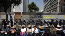 Demonstrators sit in front of riot policemen during a protest against the energy reform bill outside the Senate building in Mexico City