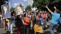 A government supporter hold pictures of former Cuban President Fidel Castro and his brother in Havana