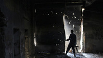 A Free Syrian Army fighter carries his weapon as he peeks out from a damaged shop in Aleppo