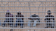 File photo of African would-be immigrants sitting on the Egyptian side of the border fence between Israel and Egypt
