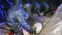 A riot police officer checks on a protester in Kiev