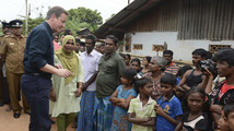 Britain's Prime Minister Cameron talks with Tamil people at the Sabapathi Pillay Welfare Centre in Jaffna