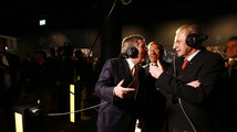 IOC President Bach speaks to his predecessor Rogge in a new presentation room at the Olympic Museum in Lausanne