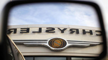 The Chrysler logo is reflected in the rear view mirror of a vehicle on the lot at Clark Chrysler Jeep Dodge dealership in Methuen