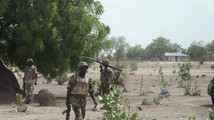 Soldiers walk through Hausari village during a military patrol near Maiduguri
