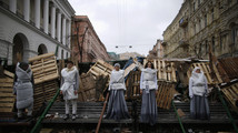 Models pose at a barricade as they take part in a photo shoot for an art project, at Independence Square in Kiev