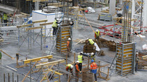 Workers are seen at a construction site of a building which will house apartments and offices in central Brussels