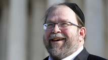 Rabbi Ginsberg smiles as he talks to reporters about his case following arguments before the U.S. Supreme Court in Washington
