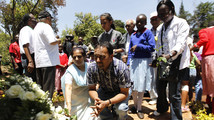Relatives pray after laying a wreath at a plaque at the Amani Garden within the Karura forest for the victims killed during the Westgate shopping mall attack in Nairobi