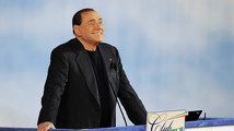 Former Italian PM Berlusconi reacts as he attends a rally to launch the