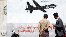 File photo shows men looking at graffiti showing a U.S. drone on a wall in Sanaa
