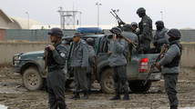 Afghan policemen stand at the site of a suicide bomb attack in Kabul