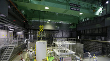 Workers work on a crane for a transport container inside the No. 4 reactor building in Fukushima prefecture
