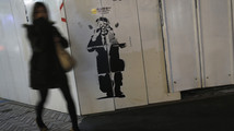 Pedestrian walks past a sticker art made by an artist known as 281 Antinuke, designed in the likeness of Japan's Prime Minister Abe, along a street in Tokyo