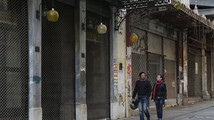 A couple walks past closed shops in Athens