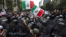 A demonstrators waves Mexican national flags during a protest against an energy reform and subway fare hike at Reforma Avenue in Mexico City