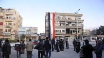 SANA handout shows a Syrian national flag hanging off a building as residents mill around in Nabek town after forces loyal to Syria's President Assad retook control from rebel fighters