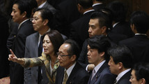 Lawmakers react after a vote on a state secrets act, towards Nakagawa, chairman of the Upper House Special Committee on National Security, at Parliament in Tokyo