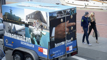 A couple pass a trailer, which is decorated with photos in the harbour of Bremerhaven