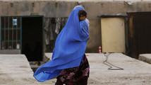 An Afghan woman wearing a burqa holds her child as she walks along a street on the outskirts of Kabul