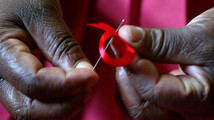 A Kenyan woman prepares ribbons ahead of December 1st, the World Aids Day at Beacon of Hope centre in ...