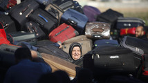 Palestinian passenger, hoping to cross into Egypt, searches for bag as she waits at Rafah crossing, between Egypt and southern Gaza Strip