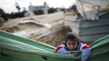 File picture of a boy leaning over tarpaulin in the Bedouin village of Bir Mshash in Israel's southern Negev