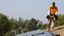 Vivint Solar technician Aguilar lays a copper line while installing solar panels on the roof of a house in Mission Viejo