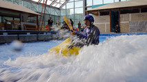A man tests the waves in a kayak in the still under-construction Surf's Up indoor water and surf park in Nashua, New Hampshire