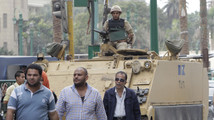 People walk in front of a soldier standing guard atop an armoured personnel carrier (APC) at Mohamed Mahmoud Street near Tahrir Square in Cairo