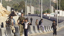 Free Syrian Army fighters carry their weapons as they watch the Syrian border crossing of Bab al-Hawa, at the Syrian-Turkish border