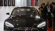 People take pictures of a Tesla Model S car, displayed at the 43rd Tokyo Motor Show