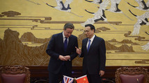 Britain's Prime Minister David Cameron and China's Premier Li Keqiang arrive at a signing ceremony in Beijing