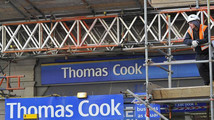 A construction worker stands on scaffolding in front of a branch of Thomas Cook in London
