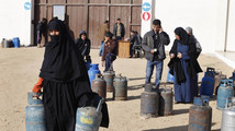 A Palestinian woman carries cooking gas canisters at a gas filling station in Rafah