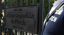 A man stands outside clothing store retailer Abercrombie & Fitch on the opening day in Paris