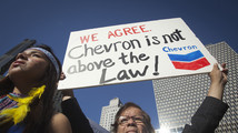 A protester holds up a sign as he demonstrates against Chevron's Racketeer Influenced and Corrupt Organizations trial in New York