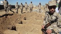 Soldiers stand by graves prepared for victims of an attack at the Defence Ministry compound in Sanaa